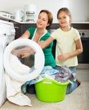 Frau mit Tochter nahe Waschmaschine Lizenzfreie Stockfotos