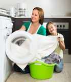 Frau mit Tochter nahe Waschmaschine Lizenzfreie Stockbilder