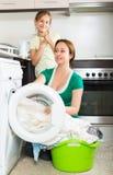Frau mit Tochter nahe Waschmaschine Stockfotos