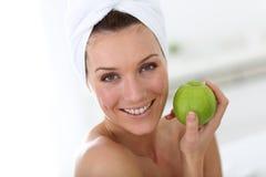 Frau mit towelk auf ihrem Kopf, der grünen Apfel hält Lizenzfreies Stockbild