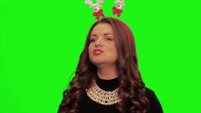 Frau mit tragendem hübschem Kleid des gelockten Haares, Weihnachtsmaterial und Halskette singt und lächelt gegen chromakey stock video footage