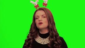 Frau mit tragendem hübschem Kleid des gelockten Haares, Weihnachtsmaterial und Halskette singt und lächelt gegen chromakey stock footage