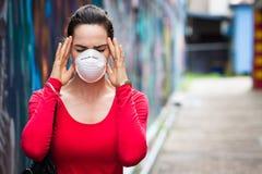 Frau mit tragender Gesichtsmaske der Kopfschmerzen Lizenzfreies Stockfoto