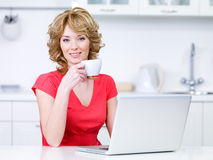 Frau mit trinkendem Kaffee des Laptops Lizenzfreie Stockbilder