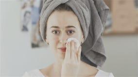 Frau mit Tuch auf Kopf reinigt die Haut des Gesichtes mit einer Baumwollauflage stock video footage