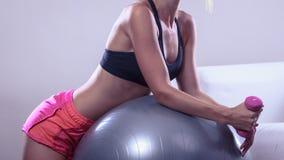 Frau mit Turnhallenball und Dummkopf, der Übung tut Lizenzfreies Stockfoto
