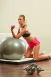 Frau mit Turnhallenball und Dummkopf, der Übung tut Stockfotos