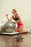 Frau mit Turnhallenball und Dummkopf, der Übung tut Stockbild