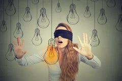 Frau mit verbundenen Augen, die durch die Glühlampen suchen nach guter Idee geht lizenzfreie stockfotografie