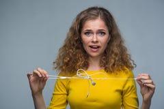 Frau mit verwirrten Drahtkopfhörern Stockbild