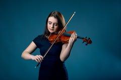 Frau mit Violine auf Hintergrund des blauen Graus stockfotografie
