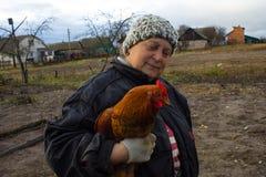 Frau mit Vogelhuhn auf Händen in der Landschaft Hintergrund Stockfotos