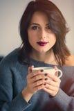 Frau mit von des Kaffees oder des Tees zu Hause Stockfotografie