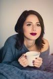 Frau mit von des Kaffees oder des Tees zu Hause Stockbilder