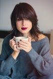 Frau mit von des Kaffees oder des Tees zu Hause Stockfoto