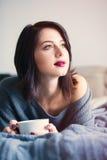 Frau mit von des Kaffees oder des Tees zu Hause Lizenzfreie Stockfotos
