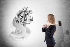 Frau mit Vorschlaghammer zerschmettert Dollarzeichen Lizenzfreies Stockfoto