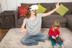 Frau mit VR-Kopfhörer und -kind mit Tablette Stockfotografie