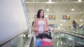 Frau mit Warenkorb auf Rolltreppe im Mall stock video