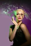 Frau mit Wasser, das auf ihren Kopf in Form des Haares spritzt Lizenzfreies Stockbild