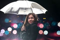 Frau mit weißem Regenschirm in den Blitzlichtern und in den Regentropfen Stockfotografie