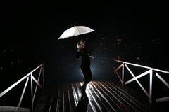 Frau mit weißem Regenschirm in den Blitzlichtern und in den Regentropfen Lizenzfreies Stockfoto