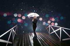 Frau mit weißem Regenschirm in den Blitzlichtern und in den Regentropfen Lizenzfreies Stockbild
