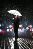 Frau mit weißem Regenschirm in den Blitzlichtern und in den Regentropfen Stockfotos