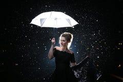 Frau mit weißem Regenschirm in den Blitzlichtern und in den Regentropfen Stockbilder