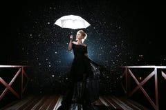 Frau mit weißem Regenschirm in den Blitzlichtern und in den Regentropfen Lizenzfreie Stockfotografie