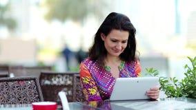 Frau mit weißem Tablet-Computer sitzt an einem Tisch in einem Café stock footage
