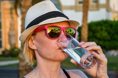 Frau mit weißem Hut und rosa Sonnenbrille mit netter Reflexion von Palmen und Sonnenuntergang frisches reines Wasser trinkend lizenzfreie stockfotografie