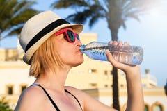 Frau mit weißem Hut und rosa Sonnenbrille neue reine Wasseraußenseite trinkend lizenzfreie stockfotos