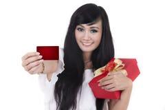 Frau mit Weihnachtsgeschenk und einer unbelegten Karte stockbild