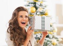 Frau mit Weihnachtspräsentkarton vor Weihnachtsbaum Stockfotografie
