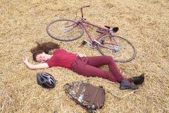 Frau mit Weinlesefahrrad, -backbag und -sturzhelm im Heu lizenzfreie stockbilder