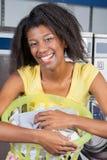 Frau mit Wäschekorb am Waschautomaten Stockbild