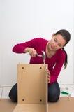 Frau mit zusammenbauenden Möbeln des Hammers Stockfoto