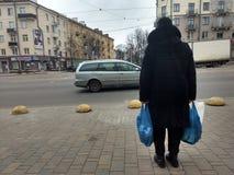 Frau mit zwei großen blauen Plastiktaschen stockfotografie