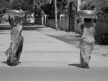 Frau mit zwei Indern, die enorme Schüssel auf Straße verkauft Stockbild