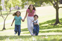Frau mit zwei jungen Kindern, die das Lächeln laufen lassen Lizenzfreie Stockfotografie
