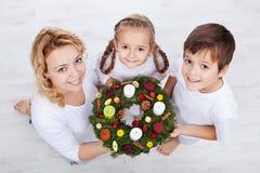 Frau mit zwei Kindern, die Aufkommen Wreath anhalten Stockfotografie