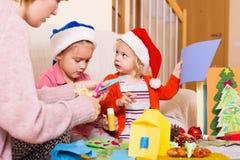 Frau mit zwei Mädchen, die für Weihnachten sich vorbereiten Stockfoto