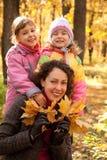 Frau mit zwei Mädchen und Ahornblättern im Park Lizenzfreies Stockfoto