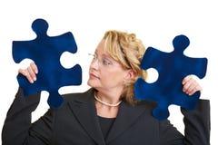 Frau mit zwei Puzzlespielstücken Stockbild