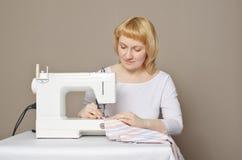 Frau näht auf der Nähmaschine stockfotografie