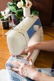 Frau näht auf einer Nähmaschine stockbild