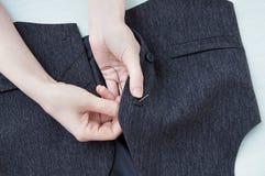 Frau näht einen Knopf zur männlichen Weste mit einer Nadel lizenzfreies stockfoto