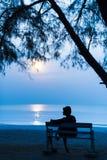 Frau nachts mit dem Mond auf dem Strand Stockbild