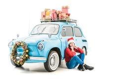 Frau nahe Auto mit Weihnachtsgeschenken Lizenzfreies Stockfoto